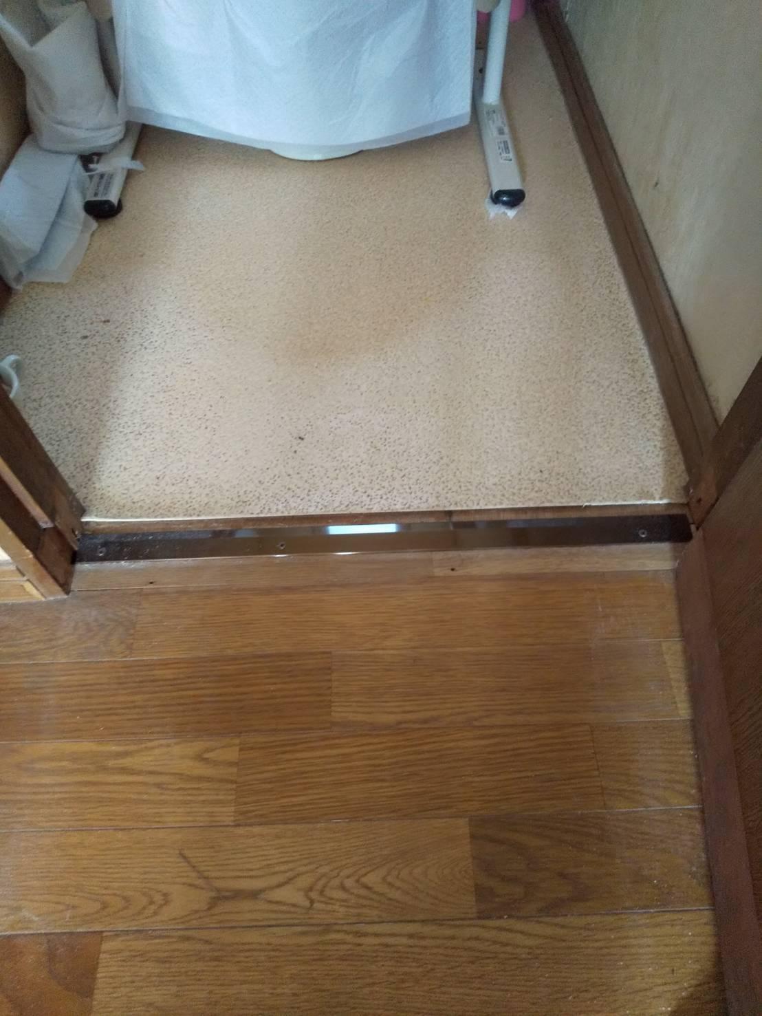 つまずきを防止するため、廊下からトイレの敷居を取り除き、への字型アルミプレートでフラットに
